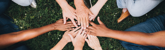 A group of people with hands in the middle